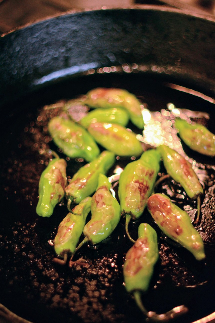 Shishito peppers blistering on a cast iron skillet